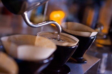 The pour-over method:  hot water is poured into filters above individual cups of coffee.